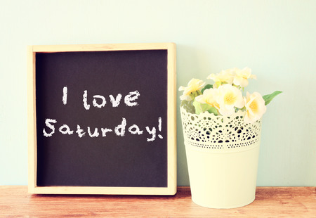 saturday: blackboard with the phrase i love saturday written on it over wooden shelf    Stock Photo