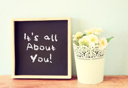 cotizacion: pizarra con la frase que s todo sobre usted escrito en �l m�s de estanter�a de madera y flores Foto de archivo