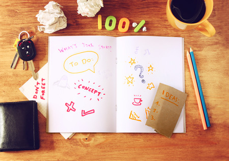 top view of messy table with notebook with doodles, coffee cup, papers and keys  photo