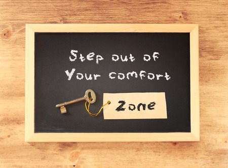 zones: the phrase step out of your comfort zone written on blackboard