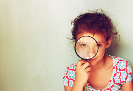 cute kid looking through magnifying glass photo