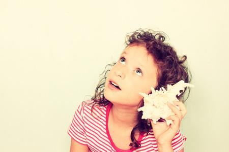 curious kid listen to seashell photo