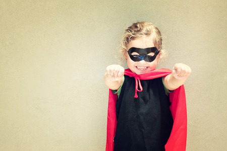 super powers: Super hero kid against textured wall background