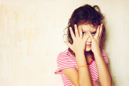 embarrassed: Shy kid peeking through covered face  filtered image    Stock Photo