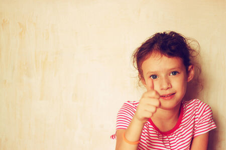 Portrait of a cute kid  girl  showing thumbs up   filtered image   photo