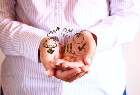 woman holding hands in cupped shape and drawing of charts and infographics. close up image with selective focus. business concept photo