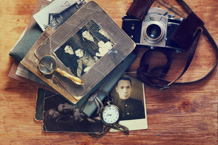 top view of old camera, antique photographs and old pocket clock photo