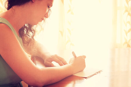 young woman sitting near window and writing. retro filtered image. photograph with natural window light