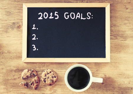 new years resolution: top view of blackboard with the phrase 2015 goals over wooden board with coffee and cookies