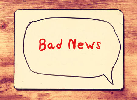 white board with the phrase bad news written on it, over wooden background. filtered image with retro effect. photo