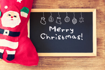 red sock and blackboard with merry christams greeting and icons