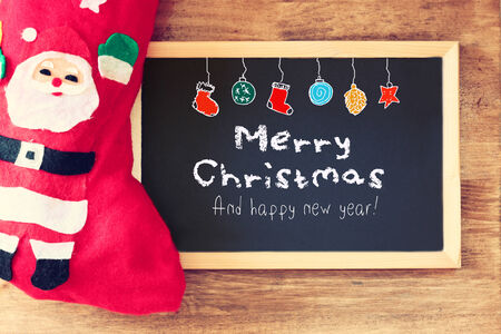 red sock and blackboard with merry christams greeting and colorful icons