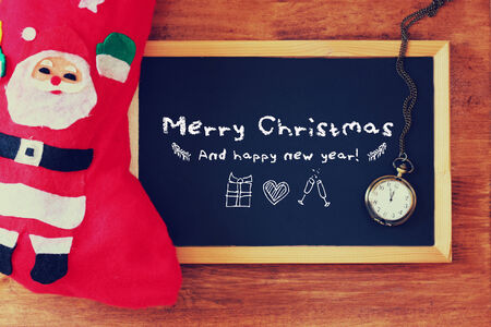 red sock and blackboard with merry christmas greeting and icons. christmas card concept photo