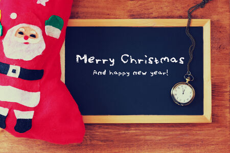 red sock and blackboard with merry Christmas greeting . christmas card concept photo
