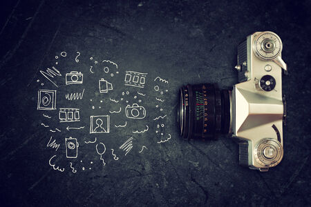 top view of old camera over blackboard and infographics sketches photo