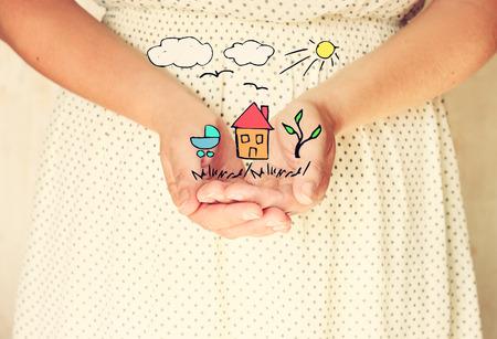 close-up van de jonge vrouw handen. uitgestrekte handen in een kom gevormde shape.sketches van huis boom en vogels als verbeelding of toekomstdromen. selectieve aandacht. retro getinte afbeelding.