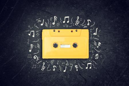 yellow retro Cassette tape over blackboard. top view. music sketches photo