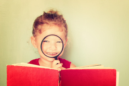 cute kid looking through magnifying glass .
