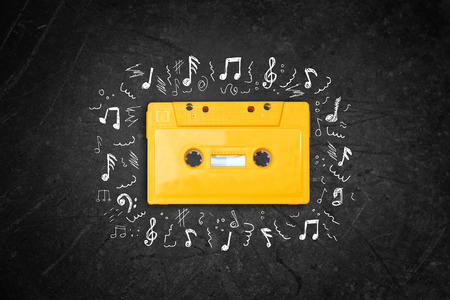 cassette tape: yellow retro Cassette tape over blackboard. top view. music sketches