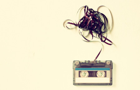 Cassette tape over wooden table with tangled ribbon. top view. retro filter 스톡 콘텐츠