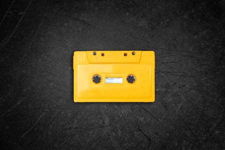 cassette tape: yellow retro Cassette tape over blackboard. top view.