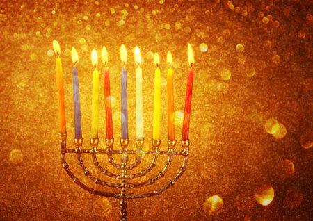 hanukka: menorah with candels and glitter lights background. hanukkah con
