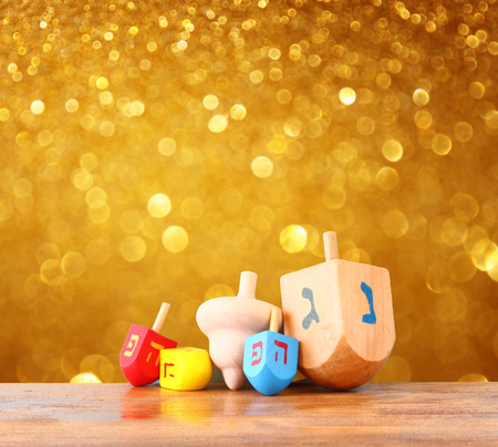 wooden dreidels for hanukkah and glitter golden lights backgroun Stock Photo