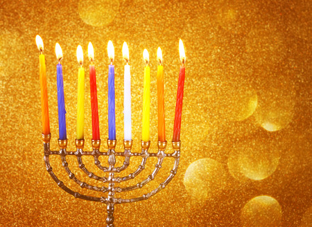 menora: jewish holiday Hanukkah background with menorah Burning candles over golden dark glitter background Stock Photo