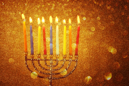 jewish holiday Hanukkah background with menorah Burning candles over golden dark glitter background Stock Photo