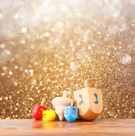 hanukkah: wooden dreidels (spinning top) for hanukkah jewish holiday over glitter gold background Stock Photo