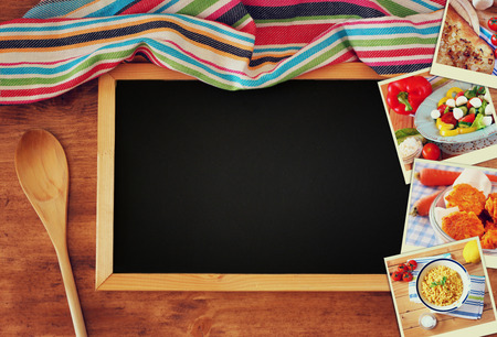 kitchen table top: Top view of blackboard and wooden spoon over wooden table and collage of photos with various food and dishes