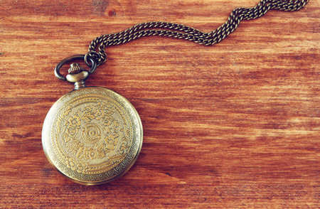 gold watch: macro image of old vintage pocket watch on wooden table. top view