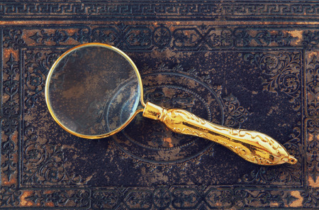 macro image of magnifying glass over antique black cover Stock Photo