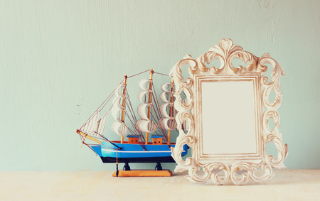 low key image of vintage antique classical frame and boat on wooden table. filtered image photo