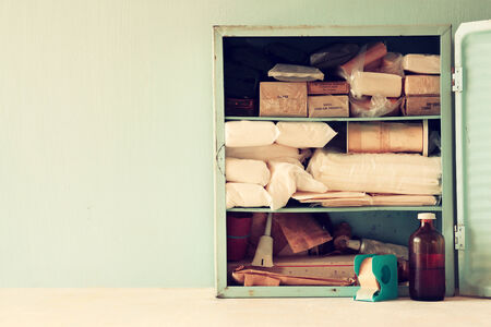 first aid kit: Vintage antique first aid kiton wooden table. filtered image