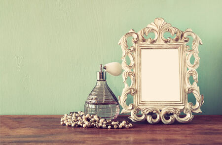 fragrant scents: Vintage antique perfume bottle with old picture frame, on wooden table. retro filtered image
