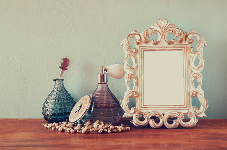 Vintage antique perfume bottles with old picture frame, on wooden table. retro filtered image photo