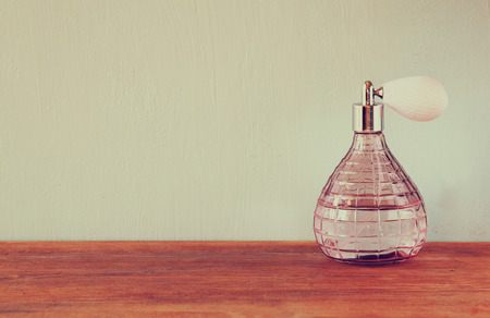 Vintage antique perfume bottle, on wooden table. retro filtered image photo