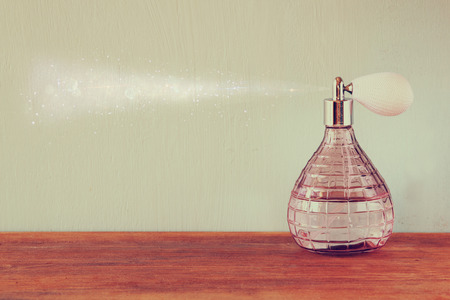 perfume spray: vintage antigue perfume bottle with effect of perfume spray, on wooden table. retro filtered image Stock Photo