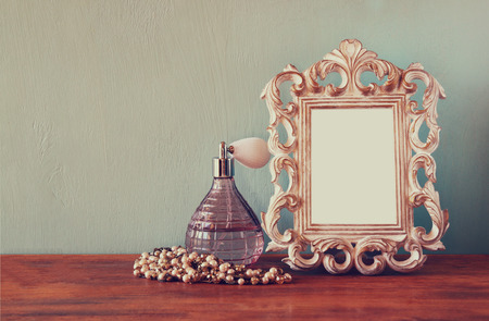 Vintage antique perfume bottle with old picture frame, on wooden table. retro filtered image photo
