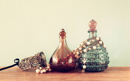 Vintage antique perfume bottles, on wooden table. retro filtered image photo