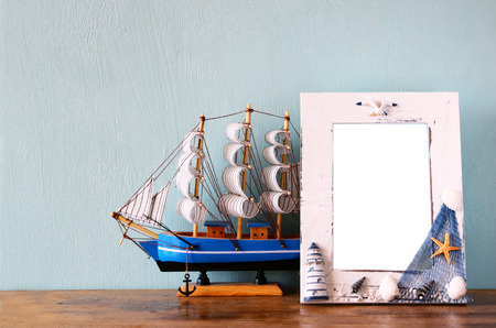 Vintage nautical frame on wooden table. retro filtered image photo