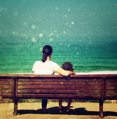 mother and child sitting on bench and looking forward at the sea photo