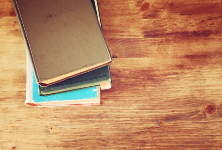 wooden table top view: Top view of old books on a wooden table. retro filtered image
