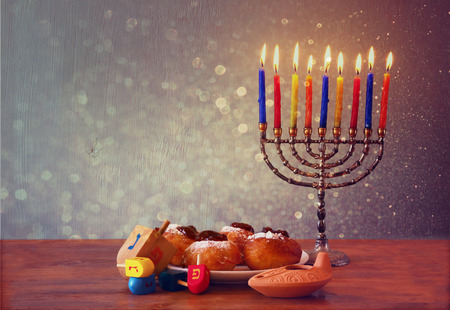 jewish holiday Hanukkah with menorah, doughnuts over wooden table. retro filtered image photo