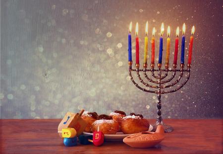 chanukah: jewish holiday Hanukkah with menorah, doughnuts over wooden table. retro filtered image