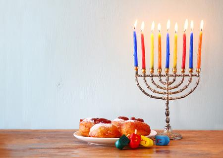 hanukah: jewish holiday Hanukkah with menorah, doughnuts over wooden table. retro filtered image