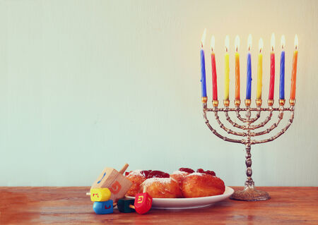 jewish holiday Hanukkah with menorah, doughnuts and wooden dreidels (spinning top). retro filtered image photo
