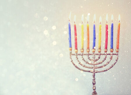 Image of jewish holiday Hanukkah background with menorah Burning candles over aqua glitter background photo