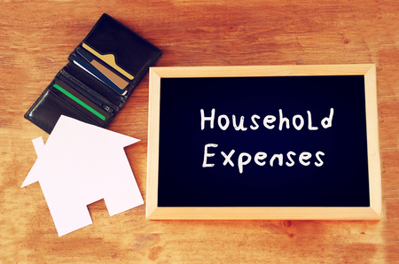 family budget: blackboard with the phrase household expenses, paper house shape and wallet with credit cards